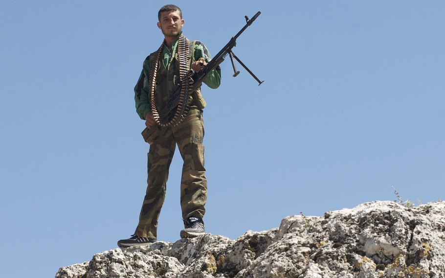 A Free Syrian Army member stands guard over an FSA base in central Syria, June 6, 2012.
