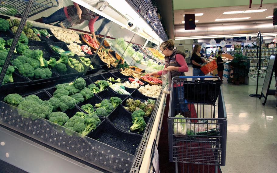 In this file photo from Jan. 8, 2013, military family member Amber Korpalski selects vegetables from the produce section of the commissary at Camp Foster, Okinawa, Japan.