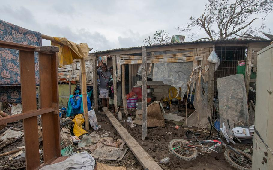 In this March 15, 2015, photo provided by UNICEF Pacific, residents stand inside damaged house after Cyclone Pam struck Mele village, on the outskirts of the capital Port Vila, Vanuatu.