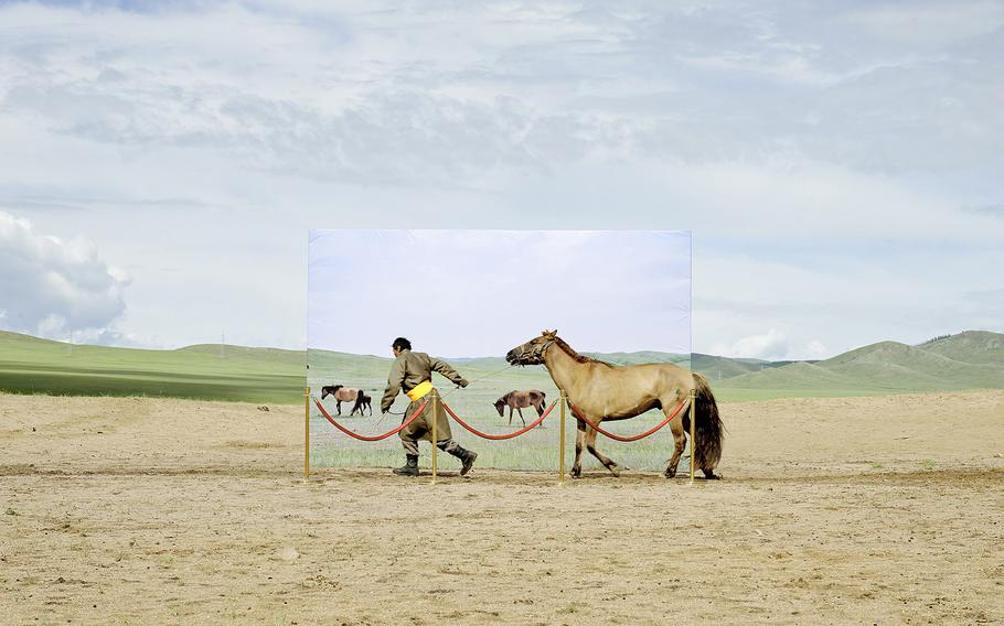 """Daesung Lee, """"futuristic archaeology 03""""   This project attempts at recreating the museum diorama with actual people and their livestock in a real place where decertifying in Mongolia. It is based on an imagination that these people try to go into museum diorama for survival in the future."""