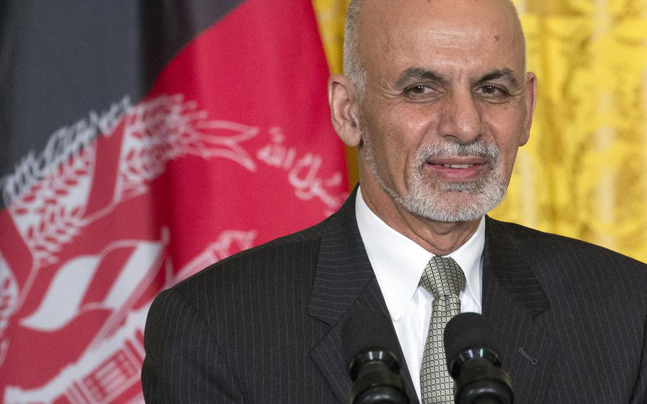 President Ashraf Ghani of Afghanistan stands in front of his nation's flag during a press conference at the White House, Mar. 24, 2015.