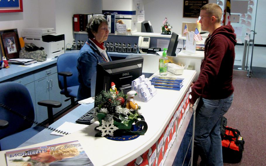 Twyla Hirrilinger, a volunteer at the USO lounge at Baltimore-Washington International Airport, greets Marine Corps Pfc. Zachary Haase as he arrives at the lounge during holiday travel Dec. 23, 2009.