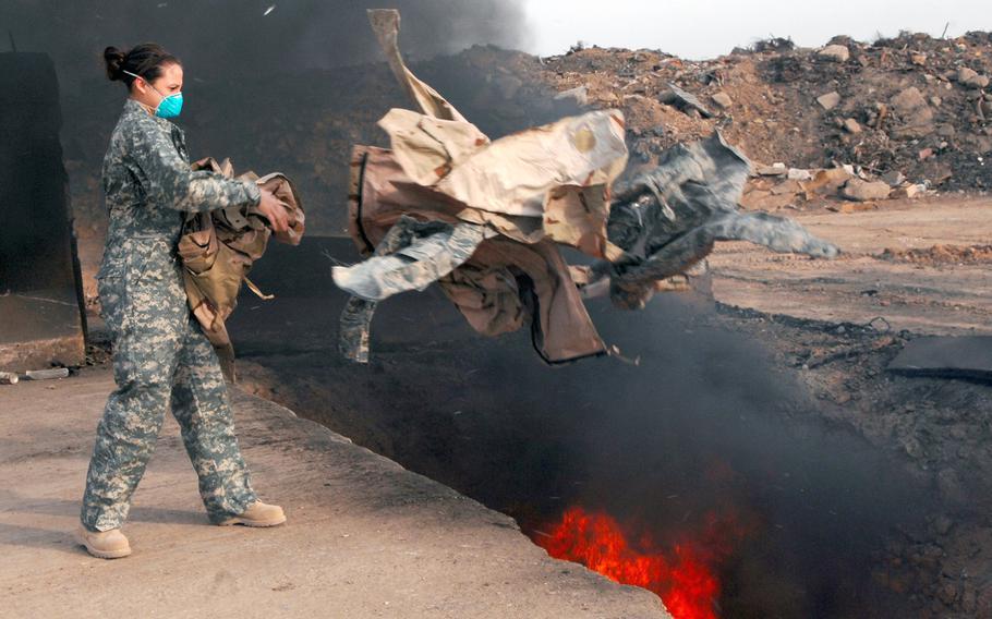 Senior Airman Frances Gavalis tosses unserviceable uniform items into a burn pit at Balad Air Base, Iraq, on March 10, 2008.