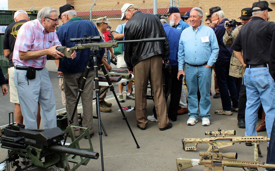 A Marine reconnaissance veteran checks out a modern sniper rifle Thursday, April 23, 2015, at Camp Pendleton, Calif. About 175 Vietnam-era recon vets reunited at Camp Pendleton for a commemoration of the 50th anniversary of the beginning of the Vietnam War.