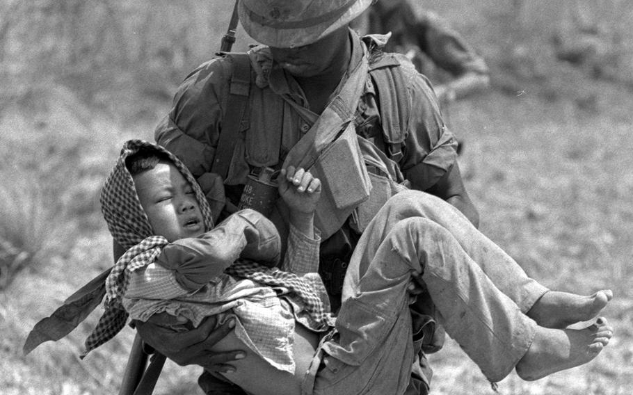 Sgt. George Edmonds carries a wounded Vietnamese boy to a helicopter.