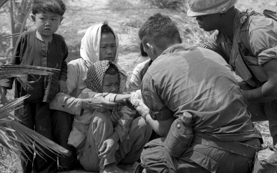A boy whose hand was accidentally shattered by an M-16 round is examined by a medic.