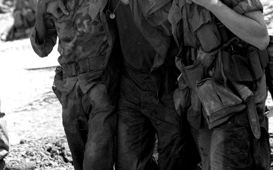 A wounded American soldier is helped to a helicopter by Vietnamese and U.S. troopers.
