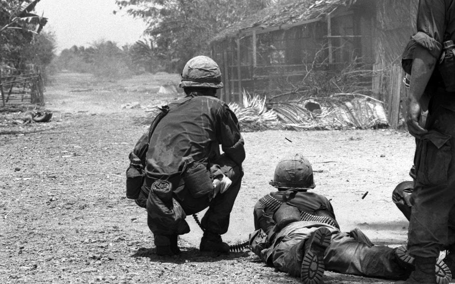 Soldiers open fire on a pair of Viet Cong on the run about 700 yards away.