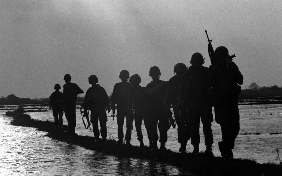 A C Co. squad is silhouetted against the sun during a patrol along a dike in a rice paddy near the Nha Be River as part of a new delta sweep.