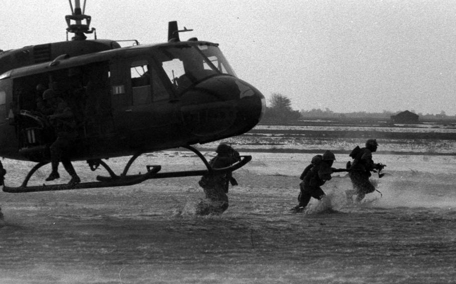 Soldiers from 199th Light Infantry Brigade splash through a rice paddy about 15 miles south of Saigon after being dropped off by a Robin Hood chopper from the 173 Assault Helicopter Co.