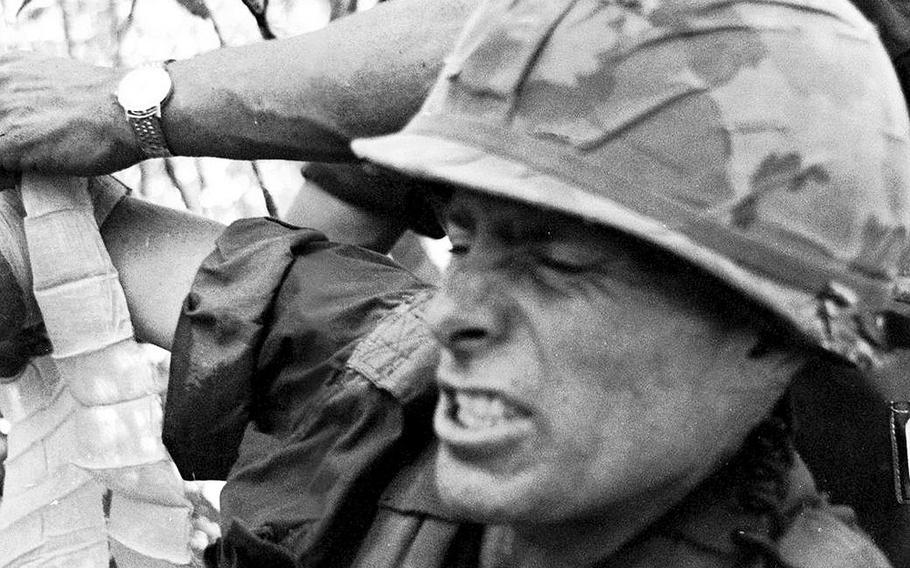Battalion commander Maj. Guy Meloy III grimaces as his wounded arm is bandaged by a radioman during fighting in an area near Dau Tieng, Vietnam, in November, 1966. Meloy, the son of a general who would himself retire as a major general, was later awarded the Distinguished Service Cross for his actions during the battle.