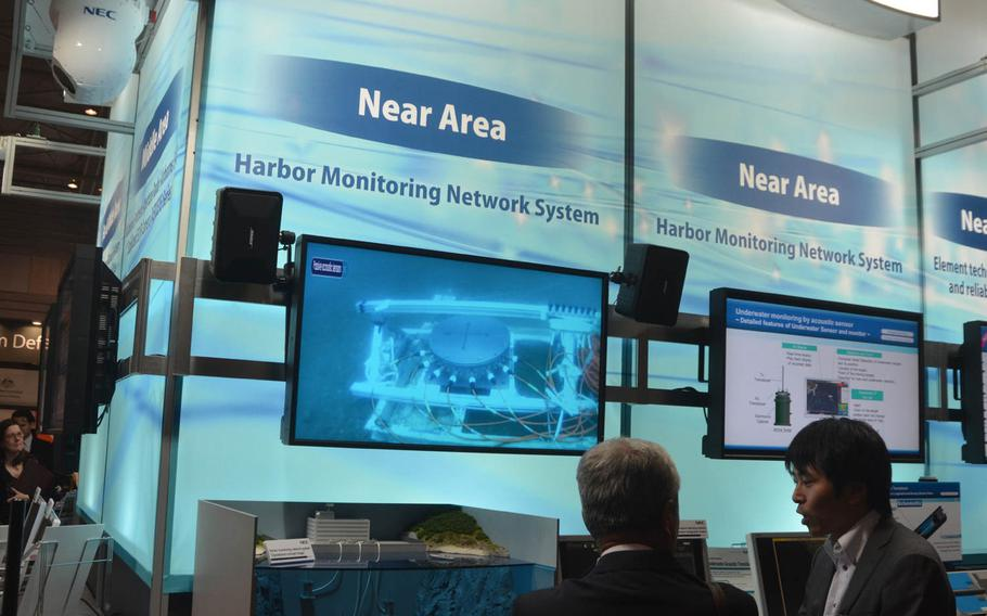 Attendees discuss a harbor monitoring system at a pavilion at the MAST conference in Yokohama, Japan, Wednesday, March 13, 2015. The three-day conference included the U.S. 7th Fleet, the Japan Self-Defense Force and military officials from around the world.