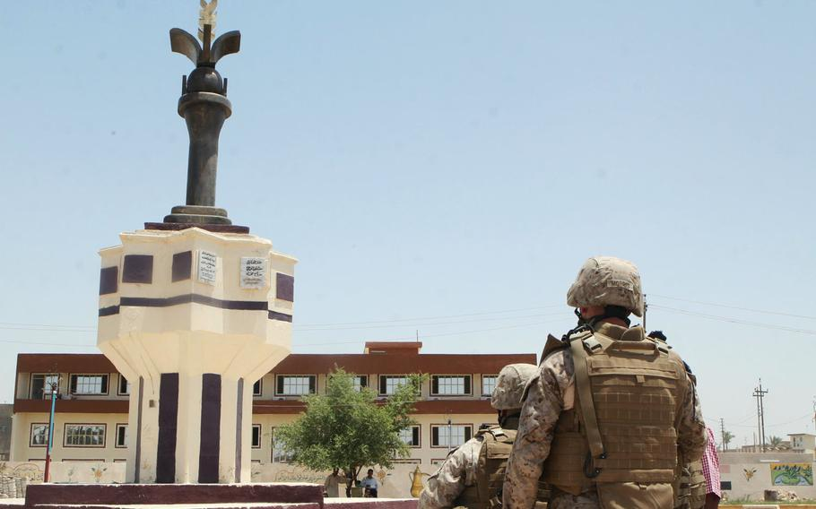In this June 2008 photo, Marines gaze at a statue donated to the city of Ramadi by a local Iraqi contractor. The contractor built the statue in a park where a statue of Saddam Hussein once stood. The statue was meant to be a symbol of peace in Ramadi.
