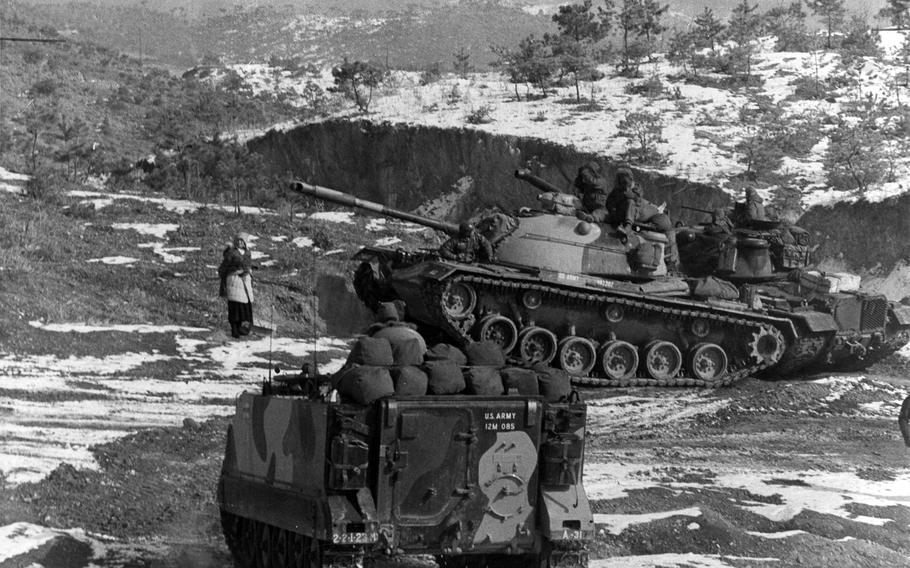 A woman pauses to watch personnel carriers and tanks from the 2nd Battalion, 23rd Infantry Regiment and 1st Battalion, 72nd Armored Regiment that were participating in an exercise on Korea's western front on Dec. 23, 1966. On July 2, 2015, units belonging to the 2nd Infantry Division's 1st Brigade Combat Team will inactivate, marking the end of more than 50 years on the peninsula.