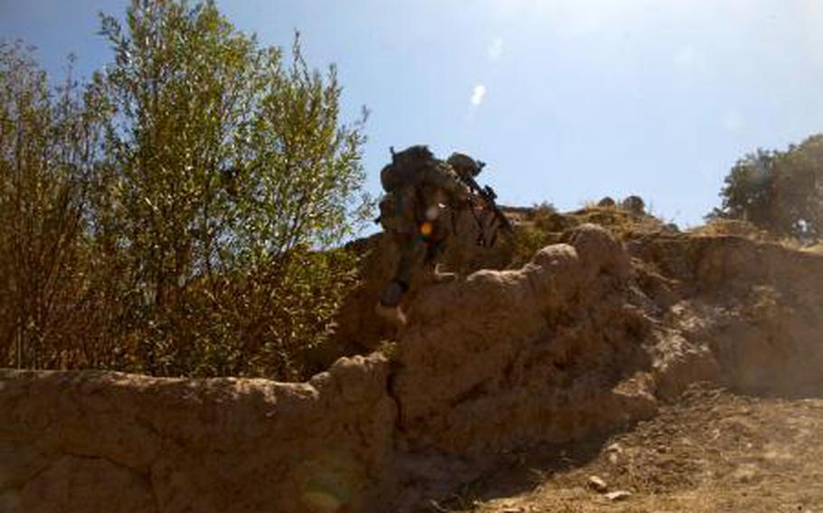 An Afghan special operator with the 5th Commando Kandak climbs a wall to gain high ground during a clearing operation Qairsar district, Faryab province, Afghanistan, Sept. 20, 2011.