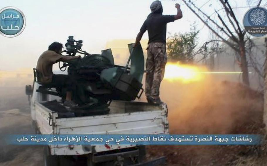 In this image posted on the Twitter page of Syria's al-Qaida-linked Nusra Front on early Tuesday, July 7, 2015, fighters from the Nusra Front fire their weapons against the Syrian government forces at the western Zahra neighborhood in Aleppo city, Syria.