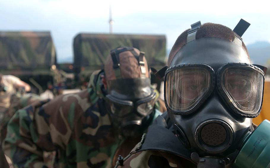 Members of the Chemical, Biological, Radiological, Nuclear, Explosives Command don gas masks in a training event on Nov. 9, 2011. The CBRNE Command typically participates in the Ulchi Freedom Guardian exercises in South Korea.
