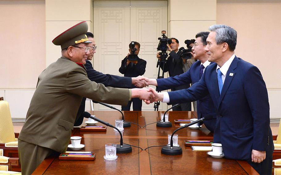 In this photo provided by the South Korean Unification Ministry, South Korean National Security Director, Kim Kwan-jin, right, and Unification Minister Hong Yong-pyo, second from right, shake hands with Hwang Pyong So, left, North Korea' top political officer for the Korean People's Army, and Kim Yang Gon, a senior North Korean official responsible for South Korean affairs, during their meeting at the border village of Panmunjom in Paju, South Korea, Saturday, Aug. 22, 2015. South Korea and North Korea agreed Saturday to hold their first high-level talks in nearly a year at a border village to defuse mounting tensions that have pushed the rivals to the brink of a possible military confrontation.
