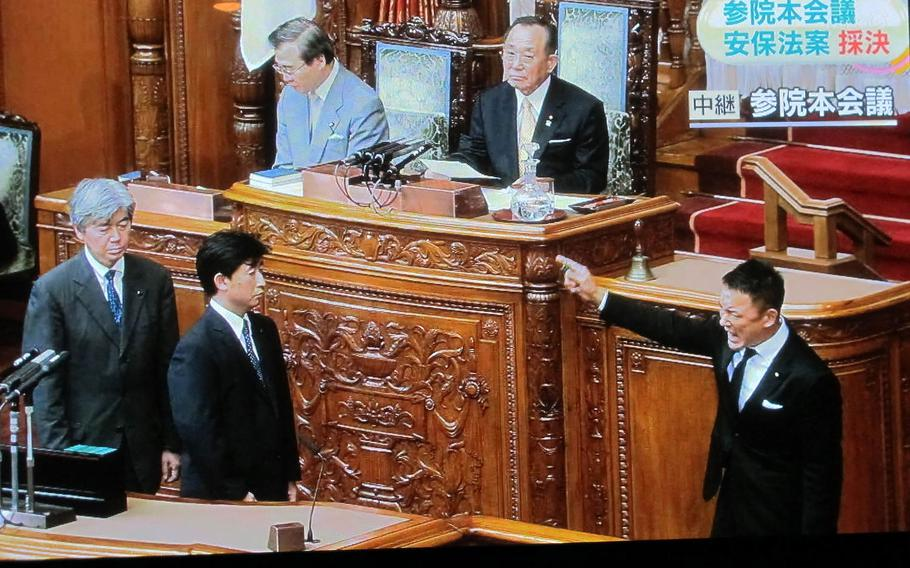 Opposition lawmaker Taro Yamamoto, right, shouts before casting his early morning vote during Japan Diet proceedings on Sept. 19, 2015. Lawmakers enacted a series of bills broadening Japan's defense powers, despite protests.