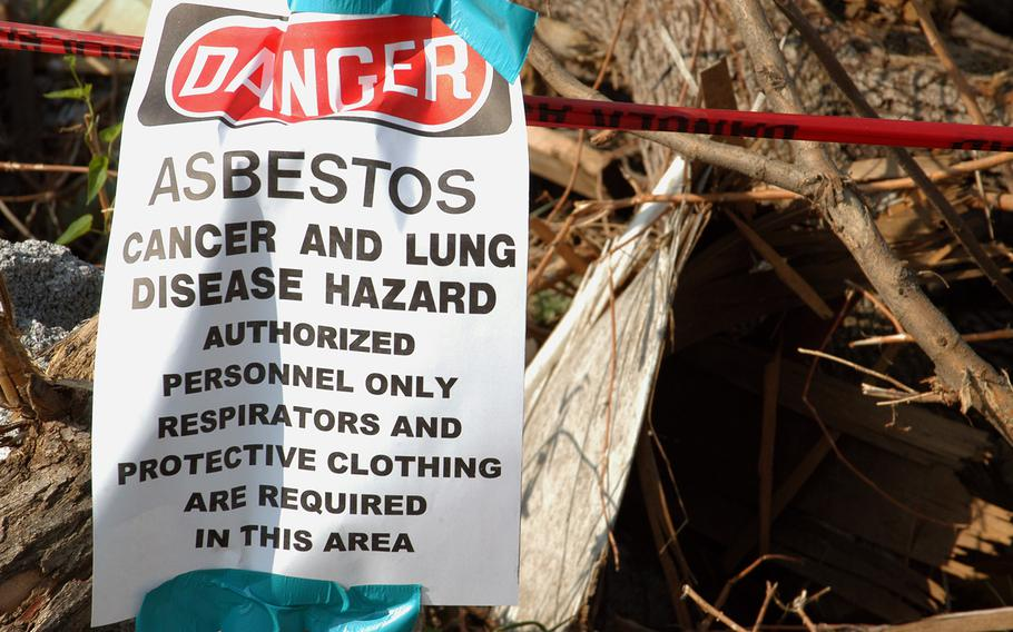 A sign warns of hazardous material as U.S. Army Corps of Engineers manage debris removal operations in Joplin, Mo., on July 29, 2011, following a deadly tornado in May 2011. A bill passed by the House in January 2016 would hand the asbestos industry a key legal advantage when fighting the claims of terminally ill veterans, critics of the legislation say.