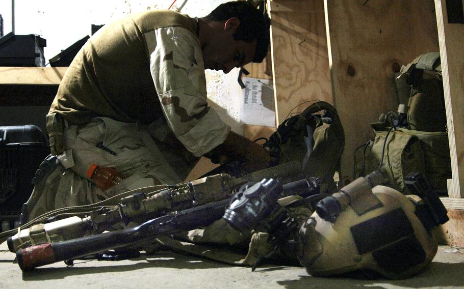 In a 2007 file photo, a U.S. Special Operations Forces member prepares his gear for an evening mission in western Iraq.