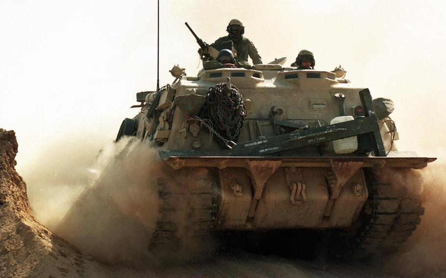 In February 1991, an armored vehicle passes through a breached sand berm separating Saudi Arabia from Iraq, paving the way for advancing allied troops during the Gulf War.