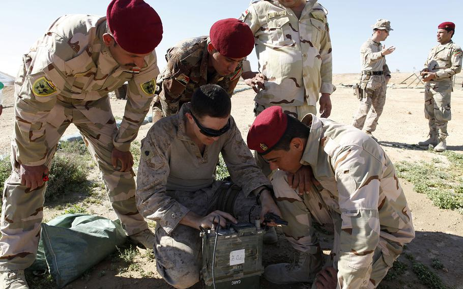 A U.S. Marine, center, demonstrates how to conduct UHF radio operations for Iraqi Soldiers with the 7th Iraqi Army Division at Al Asad Air Base, Iraq, March 2, 2016. Communication training is just one of the skills taught at Al Asad as part of the building partner capacity mission, which increases the military capabilities of Iraqi Security Forces to fight the Islamic State.