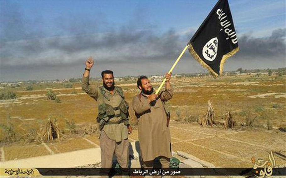 An Islamic State militant waves his group's flag as he and another celebrate in Fallujah, Iraq, west of Baghdad in a photo released on Sunday, June 28, 2015, on an Islamic State militant group website.