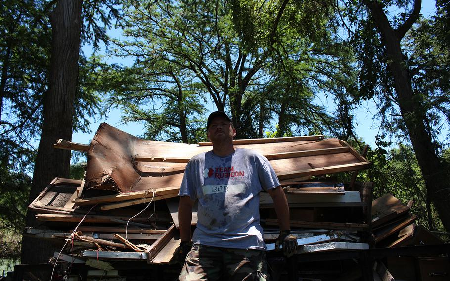 A volunteer with Team Rubicon rests following collection of debris following recent flooding in Bandera, Texas, on June 6, 2016.