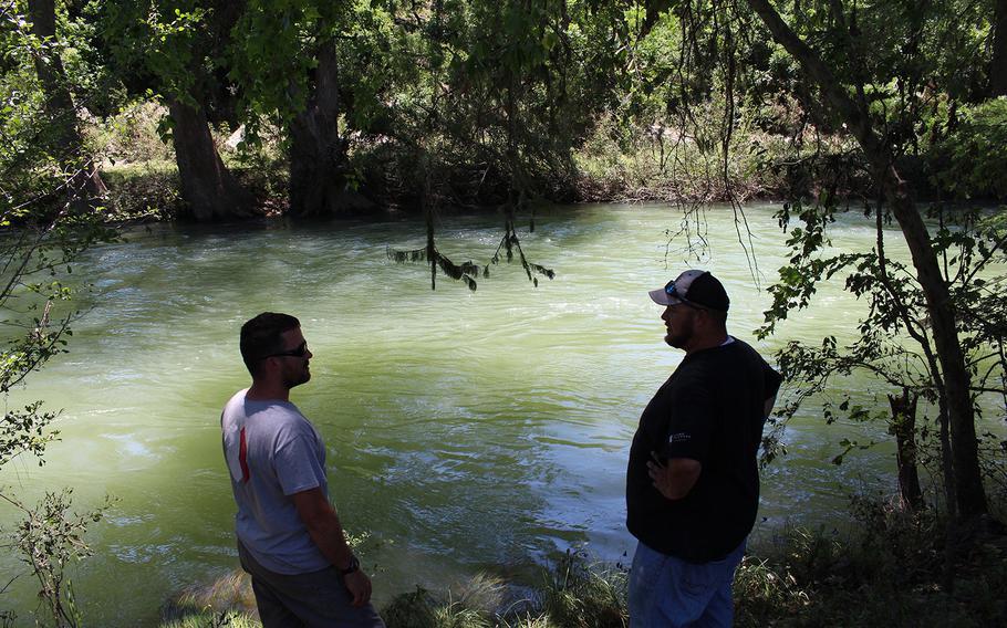 Barrett Frantzen and Jeremiah Trombly survey the Medina River following recent flooding in Bandera, Texas, on June 6, 2016.