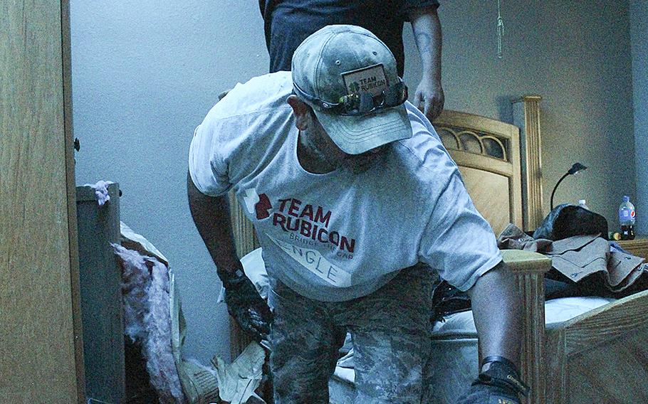 Lloyd Engle and Barrett Frantzen remove debris from a house following recent flooding in Bandera, Texas on June 6, 2016.