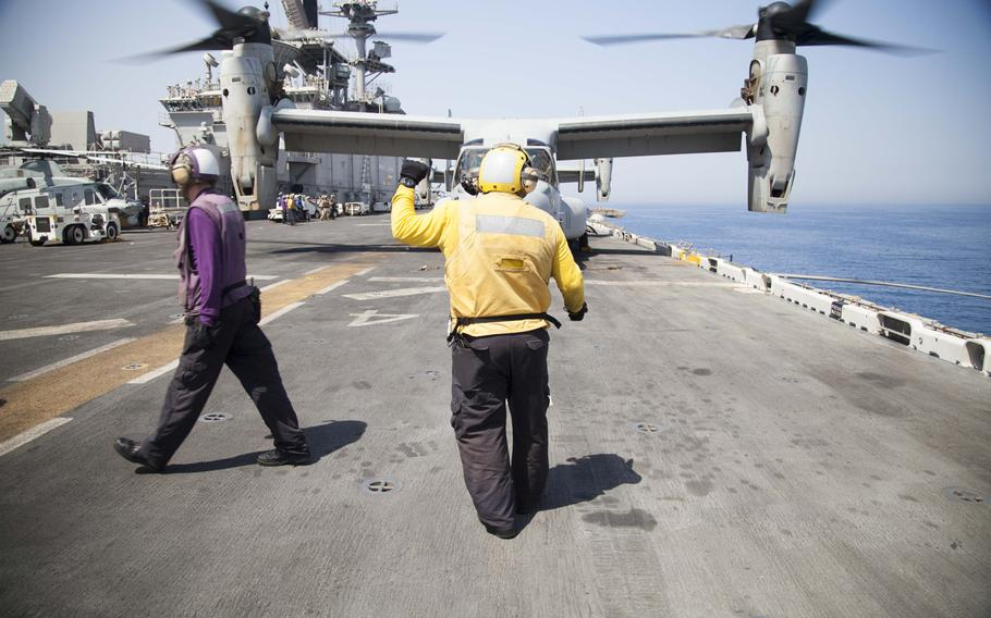 Flight deck crew personnel use hand signals to communicate with air crews and other flight deck personnel to ensure safety during flight operations on the amphibious assault ship USS Boxer on Thursday, June 16, 2016.