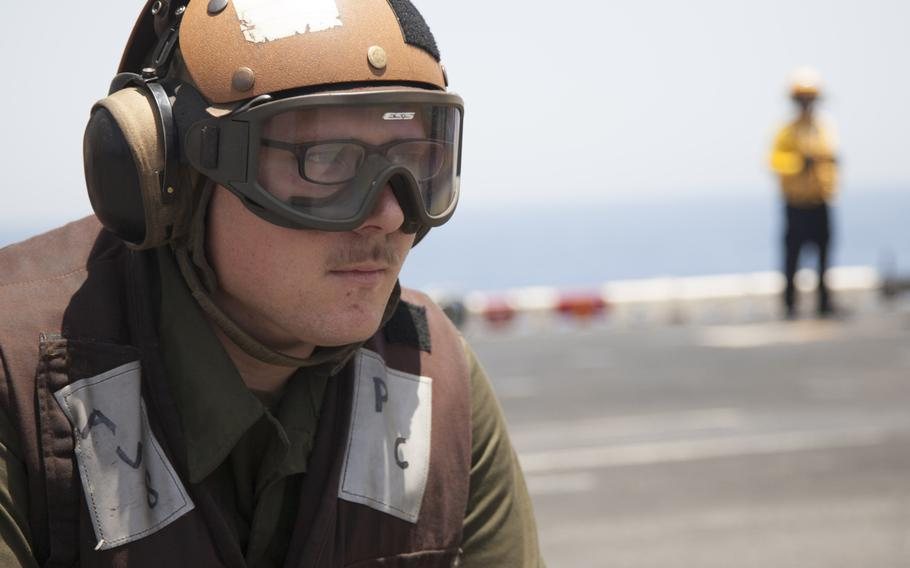 Lance Cpl. Blake Tarver, a plane captain for the 13th Marine Expeditionary Unit embarked on the amphibious assault ship USS Boxer, observes an AV-8BII Harrier prior to conducting the first aircraft sorties launched from the ship against the Islamic State in Iraq and Syria on Thursday, June 16, 2016.