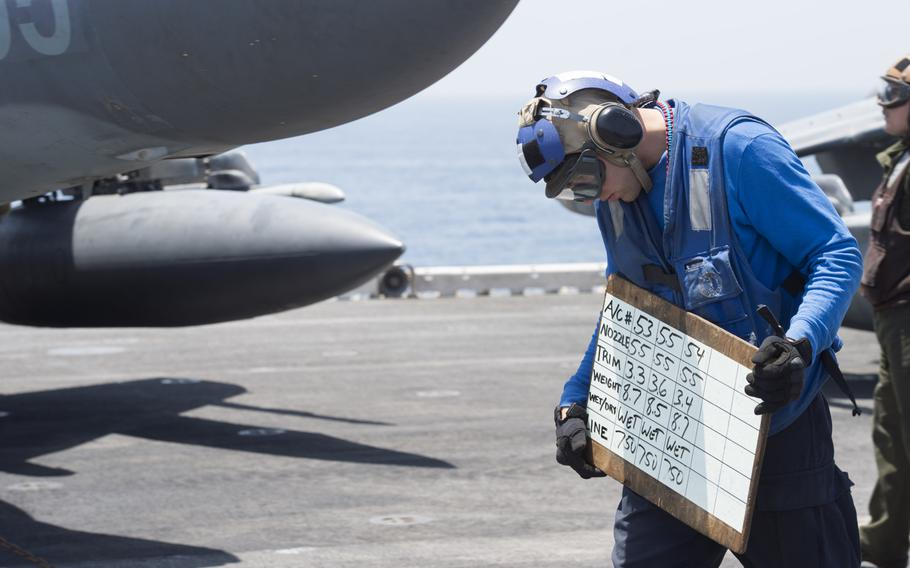 A member of the flight deck crew on the amphibious assault ship USS Boxer holds up a board to communicate with the 13th Marine Expeditionary AV-8B Harrier pilots preparing to launch in support of Operation Inherent Resolve on Thursday, June 16, 2016.