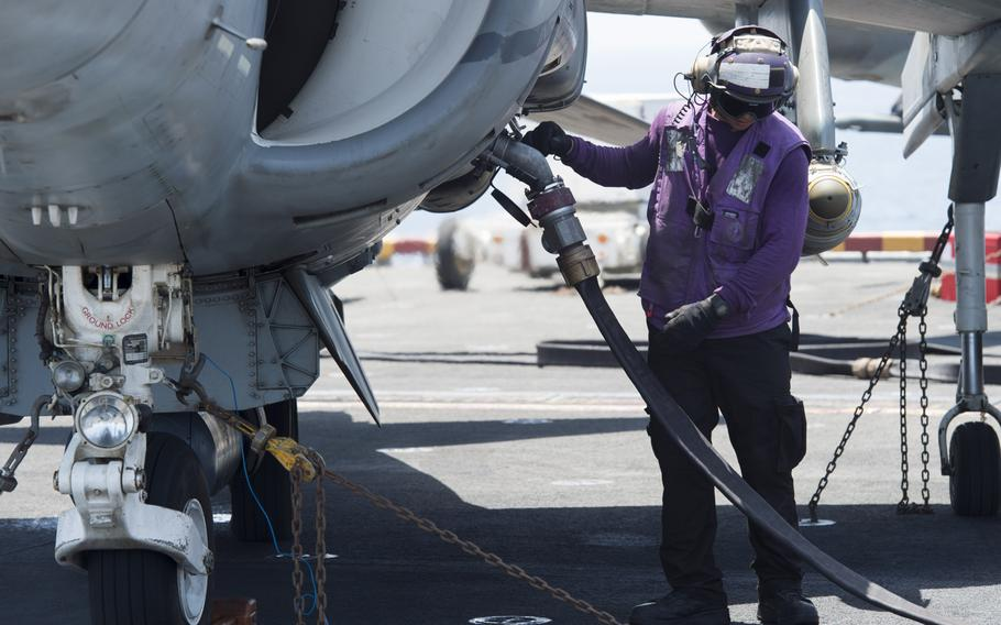 Petty Officer 3rd Class Jared Lagrimas fuels a 13th Marine Expeditionary Unit AV-8BII Harrier prior to the plane's launch from the amphibious assault ship USS Boxer on Thursday, June 16, 2016. The Harriers conducted the first airstrike sorties from the ship against the Islamic State.