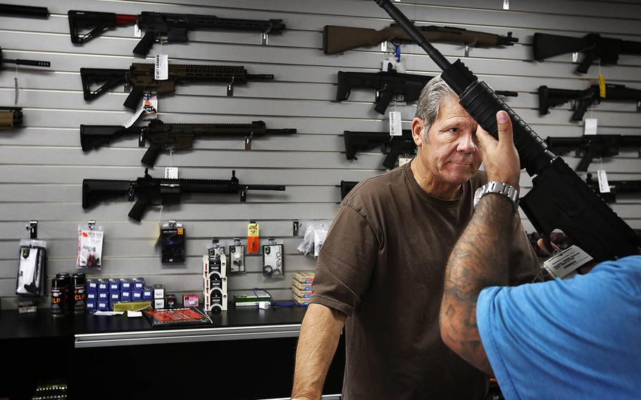 Gunsmith, Frank Cobet, of the Get Loaded gun store in Chino, Calif., shows a customer an AR-15 rifle on Tuesday, Dec. 8, 2015.