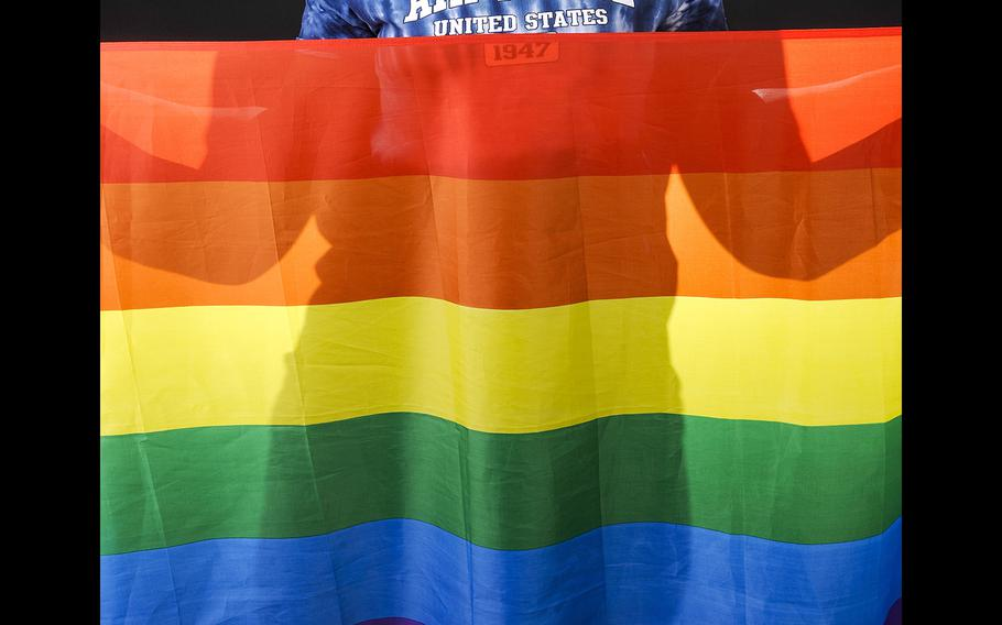 A U.S. airman holds a rainbow flag for Lesbian, Gay, Bisexual, and Transgender Pride Month during a June 12, 2014, event at Eielson Air Force Base, Alaska.