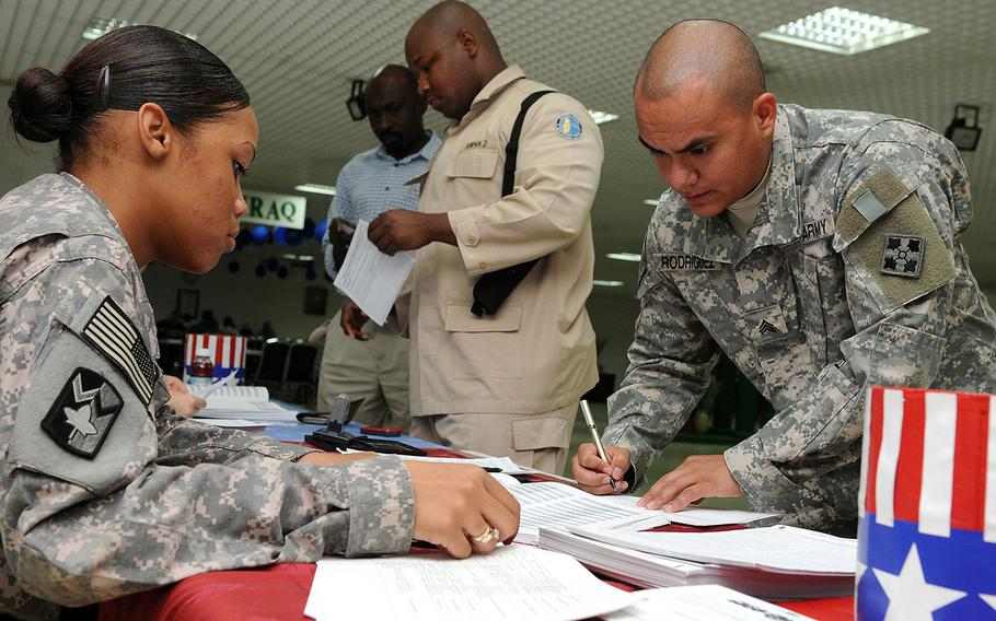 U.S. Army Pfc. Chyna Williams, from Crestview, Fla., assists Sgt. Charles Rodriguez, from Chicago, Ill., complete an absentee ballot at Camp As Sayliyah, Qatar, Oct. 16, 2008.