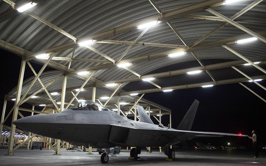 A U.S. Air Force F-22 Raptor crew chief (right) inspects the left wing during pre-flight inspection at an undisclosed location in Southwest Asia, July 11, 2016. The F-22 Raptors fly in support of Combined Joint Task Force-Operation Inherent Resolve.