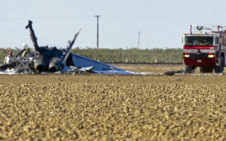 Firefighters stand by wreckage from a fighter jet where it crashed in a field near Lemoore Naval Air Station in California, Monday, Sept. 21, 2015. The pilot ejected and safely parachuted to the ground.