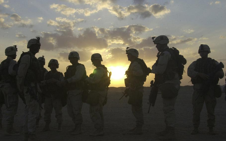 U.S. troops from Company B, 1st Battalion, 15th Infantry, are silhouetted against the sun during the push north to Baghdad in March, 2003.