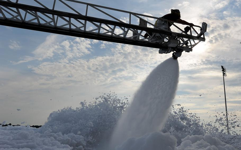 A civilian firefighter with the 436th Civil Engineer Squadron Fire Department works the nozzle of a ladder truck hose to spray foam on Sept. 16, 2013, at Dover Air Force Base, Del.