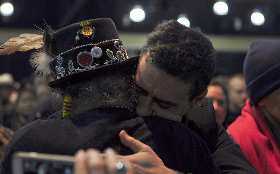 Wes Clark Jr., an organizer of Veterans for Standing Rock, hugs a member of the Standing Rock Sioux tribe during a gathering of veterans and tribal elders Monday, Dec. 5, 2016.