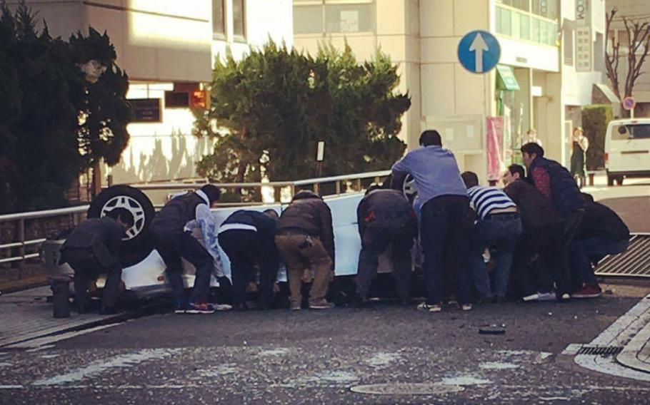 U.S. and Japanese citizens attempt to free people trapped inside a vehicle after it plunged from the fifth story of a parking garage across the street from Yokosuka Naval Base Dec. 31, 2016. Three adults died in the accident, while two children remain hospitalized.