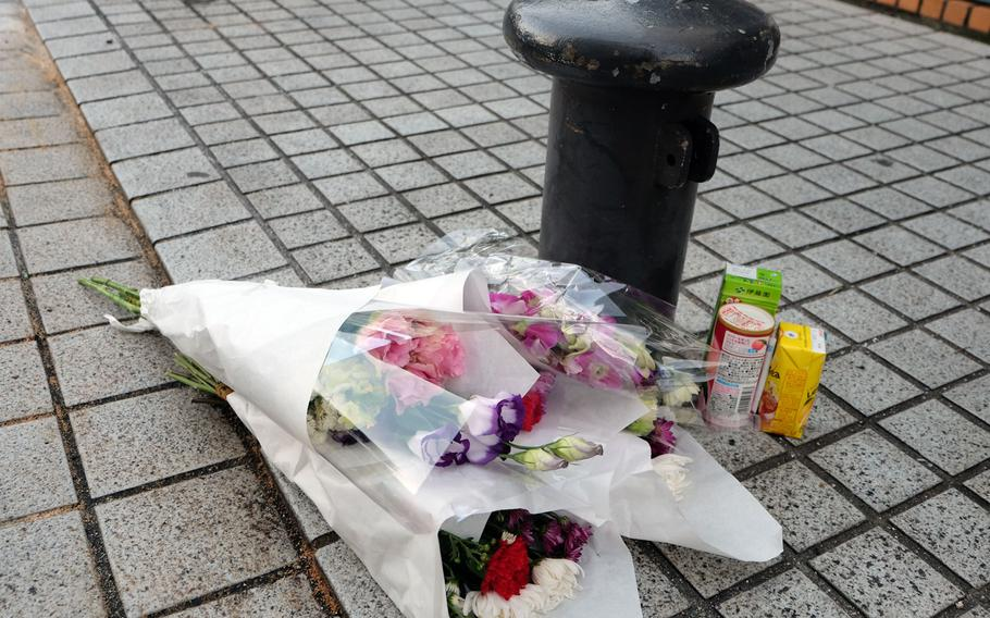 Flowers and snacks are left as a memorial at the site of a  deadly crash that left three people dead and two children seriously injured. The crash occurred Saturday, Dec. 31, 2016 at a parking garage across the street from Yokosuka Naval Base.