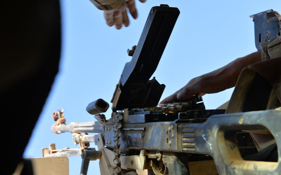 An Iraqi soldier loads a PK machine gun in the turret of an Iraqi army Humvee near Mosul, Nov. 19, 2016. Amnesty International found that Iraqi army weapons supplied by the U.S., Russia and other countries have wound up in the hands of Iran-backed Shiite militias accused of committing war crimes.