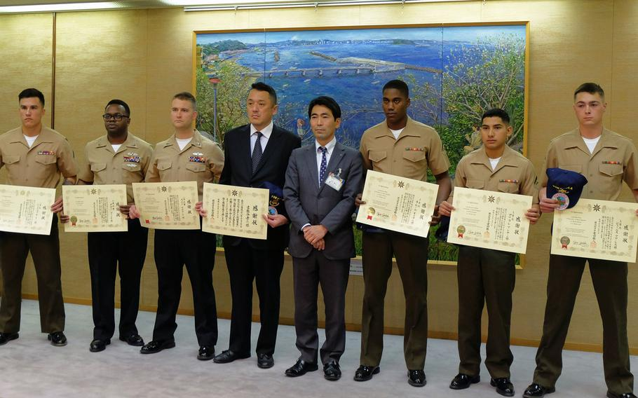 Yokosuka Mayor Yuto Yoshida poses for a photo with six servicemembers and one Japanese local who were recognized Jan. 16, 2017 for providing assistance to the victims of a deadly car crash Dec. 31, 2016.
