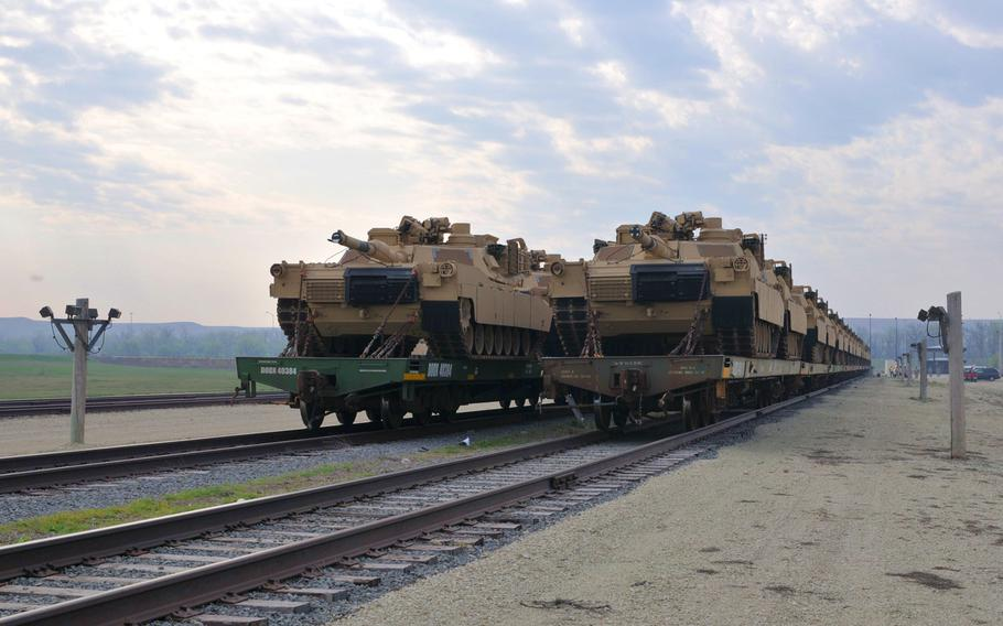 """Several dozen of the Army's """"newest"""" Abrams tanks wait to be offloaded from flatbed train cars in 2012 at Fort Riley's Railhead. A recent Congressional Research Service report said the automatic-loading 125-mm guns on the Chinese MBT-3000 and the Russian T-14 Armata could """"theoretically offer greater range and armor penetration"""" than the American 120-mm."""
