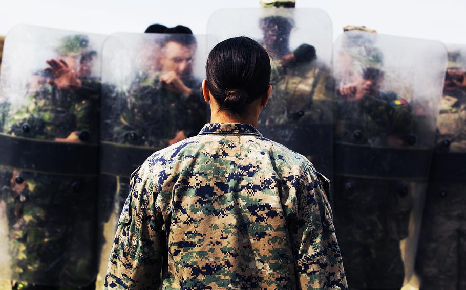 A female Marine demonstrates her capabilities in Marine Corps martial arts, non-lethal weapons, foreign weapons handling and combat lifesaving to Romanian and U.S. soldiers in Romania on Sept. 29, 2016.