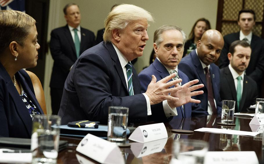 President Donald Trump, accompanied by Veterans Affairs Secretary David Shulkin, speaks during a meeting about veterans affairs, Friday, March 17, 2017, in the Roosevelt Room of the White House.